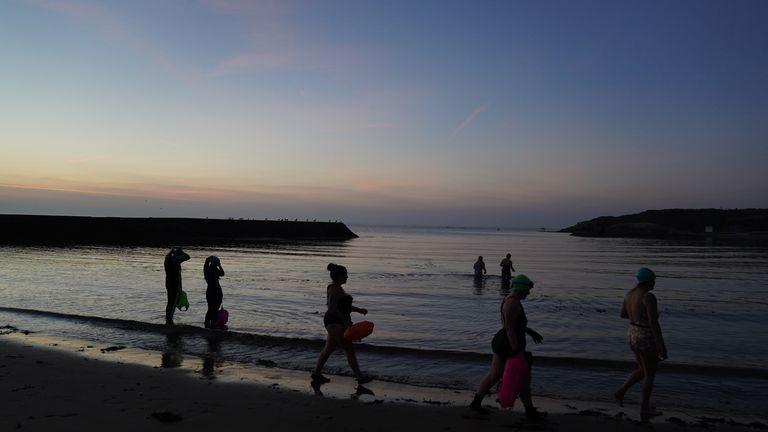 شناگران دریایی قبل از طلوع آفتاب در خلیج Cullercoats در ساحل شمال شرقی حرکت می کنند.  دمای هوا در برخی مناطق انگلستان تا 30 درجه سانتی گراد پیش بینی می شود