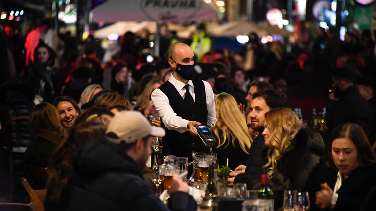 A waiter wears a face mask as people eat and drink outside restaurants in Soho, ahead of a national lockdown for England which begins on Thursday, in Chelsea, west London, Wednesday, Nov. 4, 2020. A second lockdown in England is set to come into force on Thursday. It's a big blow to businesses that sweeps away any hopes that the British economy might have recovered by the end of this year a large proportion of the near 25% drop endured in the spring PIC:AP
