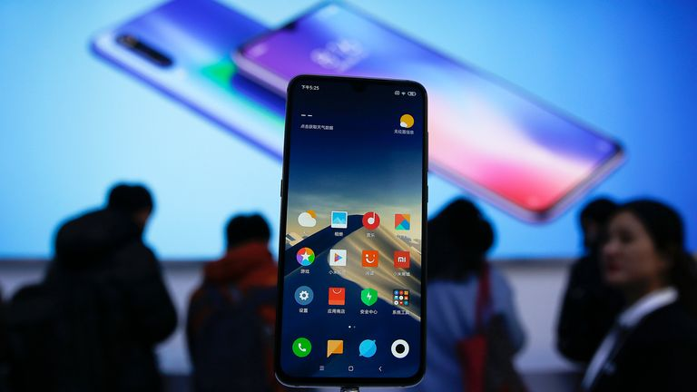 Xiaomi new model Mi 9 is displayed on an exhibition booth as invited guests try out the phones after its launch event in Beijing, Wednesday, Feb. 20, 2019. Xiaomi on Wednesday unveiled a thinner and lighter new model built with Ai triple camera that its Founder, Chairman and CEO Lei said has better performance comparable to Apple...s iPhone Xs and Huawei Mate 20. (AP Photo/Andy Wong)