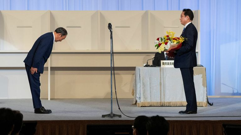 Japan's outgoing Prime Minister, Yoshihide Suga, bows to former Fumio Kishida after the election result is announced