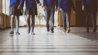 Cropped image of school kids in uniform walking together in a row through corridor. Focus on legs of students walking through school hallway.
