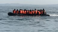 Re:Migrants  - manhandling a large inflatable boat down a northern French beach, to get to the seafront in order to to cross the Channel.  - re copy from  Adam Parsons and Sophie Garratt
