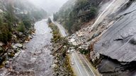 Rocks and vegetation cover Highway 70 following a landslide in the Dixie Fire zone on Sunday, Oct. 24, 2021, in Plumas County, Calif. Heavy rains blanketing Northern California created slide and flood hazards in land scorched during last summer's wildfires. (AP Photo/Noah Berger)