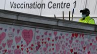 National Covid Memorial Wall, a dedication of thousands of hand painted hearts and messages commemorating victims of the COVID-19 pandemic, is seen in London A street cleaner wearing a protective face mask works in the grounds of St Thomas' Hospital, beside the National Covid Memorial Wall, a dedication of thousands of hand painted hearts and messages commemorating victims of the COVID-19 pandemic, in London, Britain, October 20, 2021. REUTERS/Toby Melville