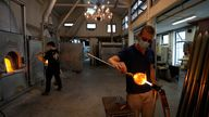 A glass-worker finishes a glass artistic creation in a factory in Murano island, Venice. Pic: AP