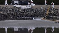 Clean-up crews work to mitigate the damage in an ecological estuary after a major oil spill off the coast of California came ashore in Huntington Beach, California, U.S. October 4, 2021