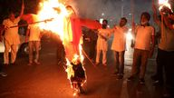 Protestors burn an effigy of Yogi Adityanath, chief minister of the northern state of Uttar Pradesh, after people were killed in the car crash