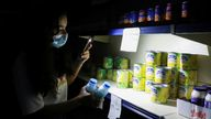 A customer uses her phone's torch light in a grocery store near the town of Bhamdoun