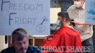 A barber cuts a man's hair on the first day of eased restrictions