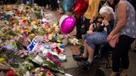 FILE - In this May 24, 2017 file photo women cry after placing flowers in a square in central Manchester, Britain, after the suicide attack at an Ariana Grande concert that left more than 20 people dead and many more injured, as it ended on Monday night at the Manchester Arena. (AP Photo/Emilio Morenatti, File)