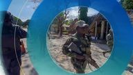 In this image made from video, a Rwandan policeman, left, and Mozambican military, right, patrol near the Amarula Palma hotel in Palma, Cabo Delgado province, Mozambique Sunday, Aug. 15, 2021. Rwanda's troops have rapidly helped Mozambique's armed forces achieve victories against Islamic extremists, who have created a humanitarian emergency in northern Cabo Delgado province and surrounding areas. (AP Photo/Marc Hoogsteyns)