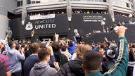 Jubilant Newcastle United fans celebrate the club's Saudi takeover outside the stadium.