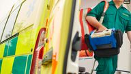 a uk ambulance staff member emerges from the back of an ambulance with his emergency backpack , and vital signs monitor . Pic: iStock