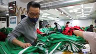 """Ko Jong-hyun, 59, a clothing factory owner, checks newly produced tracksuits inspired by Netflix series """"Squid Game"""" at his plant in Seoul, South Korea"""