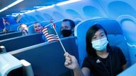 Passengers wearing protective masks hold American and British flags before a JetBlue flight to London at JFK International Airport, 11  August, 2021