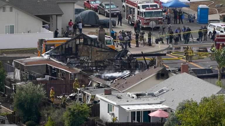 Emergency crews work a the scene of a small plane crash, Monday, Oct. 11, 2021, in Santee, Calif. Authorities say at least two people were killed and two others were injured when the plane crashed into a suburban Southern California neighborhood, setting two homes ablaze. (AP Photo/Gregory Bull)