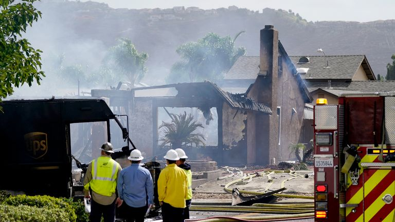 Fire and safety crews work the scene of a plane crash, Monday, Oct. 11, 2021, in Santee, Calif. At least two people were killed and two others were injured when the small plane crashed into a suburban Southern California neighborhood, setting two homes ablaze, authorities said. (AP Photo/Gregory Bull)