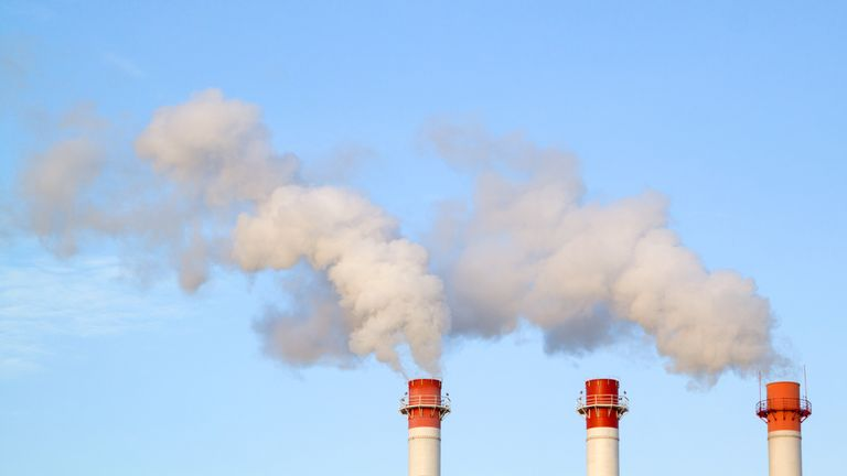 Smoking industrial stacks in a thermal power plant emit polluted air into the atmosphere in the blue sky