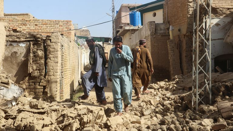 Residents walk amid the rubble of damaged houses along a street following an earthquake in Harnai, Balochistan, Pakistan, October 7, 2021. REUTERS/Naseer Ahmed