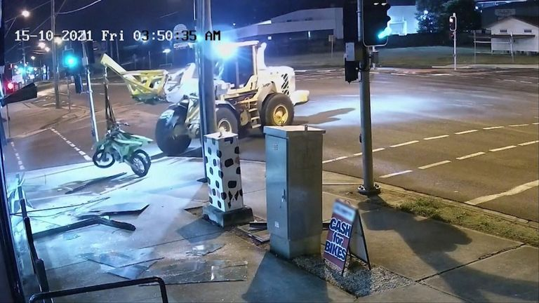 Front end loader smashes through shop window and make off with motorbikes