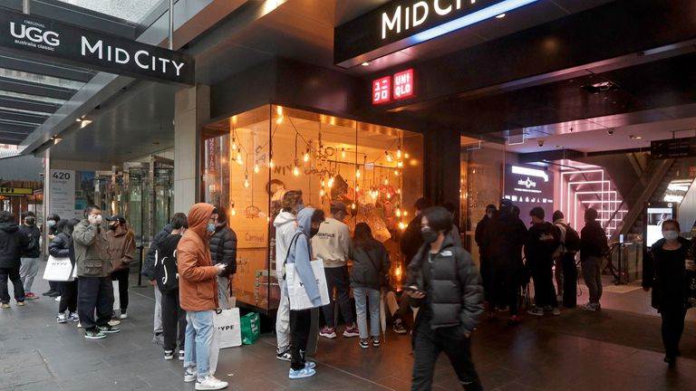 Customers line up to enter a store in the central business district after more than 100 days of lockdown to help contain the COVID-19 outbreak in Sydney, Monday, Oct. 11, 2021. (AP Photo/Rick Rycroft)..