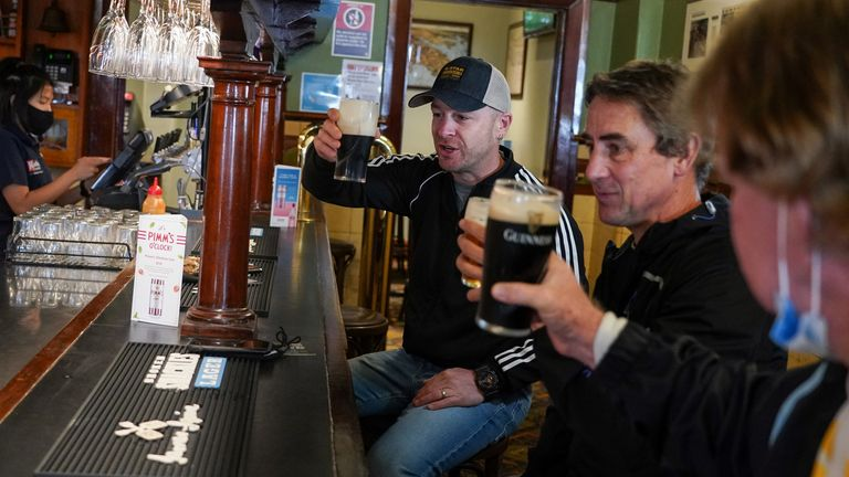 (L-R) Customers Brian O'Mara, Darrell Forman and Doug Thomas drink beers together at the Fortune of War pub, on the first morning of pubs and many other businesses re-opening to vaccinated people, following months of lockdown orders to curb an outbreak of the coronavirus disease (COVID-19), in Sydney, Australia, October 11, 2021. REUTERS/Loren Elliott