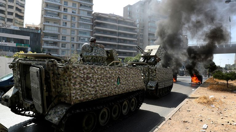 Pic: AP Lebanese army soldiers stand guard on their armored vehicle as supporters of the Shiite Hezbollah and Amal groups burn garbage containers to block a road during a protest in Beirut, Lebanon, Thursday, Oct. 14, 2021. Armed clashes broke out in Beirut Thursday during a protest against the lead judge investigating last year's massive blast in the city's port, as tensions over the domestic probe boiled over. (AP Photo/Bilal Hussein)
