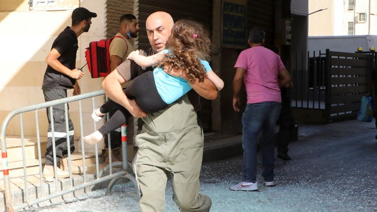 A man carrying a girl evacuates after gunfire erupted, in Beirut, Lebanon October 14, 2021. REUTERS/Mohamed Azakir