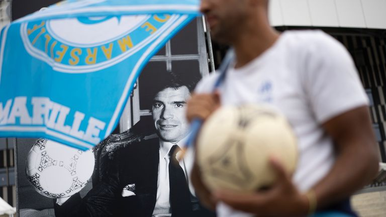 People gather close to an image of Bernard Tapie outside the Orange Velodrome stadium in Marseille,
