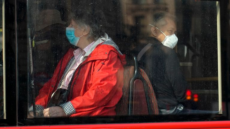 People wear face masks as they sit on a bus, in London, Tuesday, Oct. 19, 2021. Many scientists are pressing the British government to re-impose social restrictions and speed up booster vaccinations as coronavirus infection rates, already Europe's highest, rise once more. The U.K. recorded 49,156 new COVID-19 cases on Monday, Oct. 18, the largest number since mid-July. New infections averaged 43,000 a day over the past week, a 15% increase on the week before.(AP Photo/Alberto Pezzali)