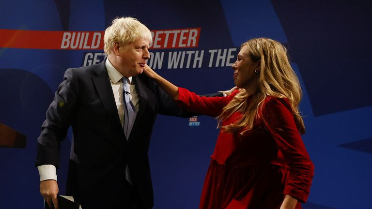 Britain's Prime Minister Boris Johnson embraces his wife Carrie Johnson after delivering a speech during the annual Conservative Party Conference, in Manchester, Britain, October 6, 2021. REUTERS/Phil Noble