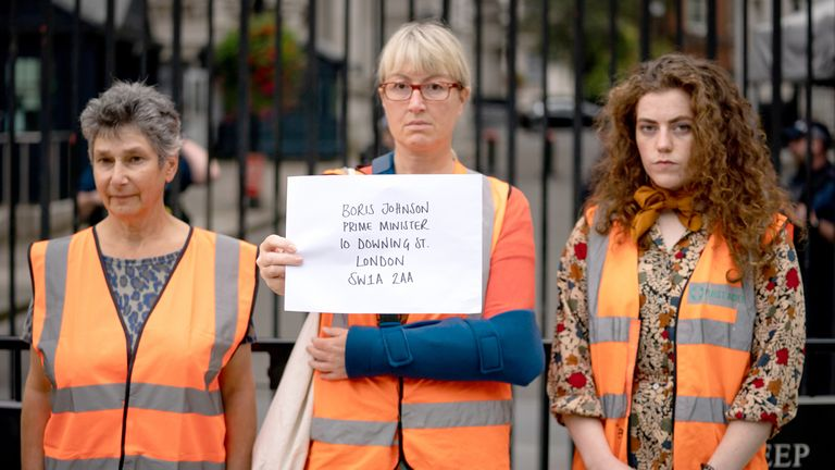 Protesters stand outside Downing Street with their letter.