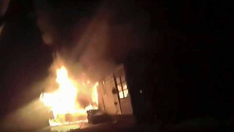 Police officer drags woman from burning house