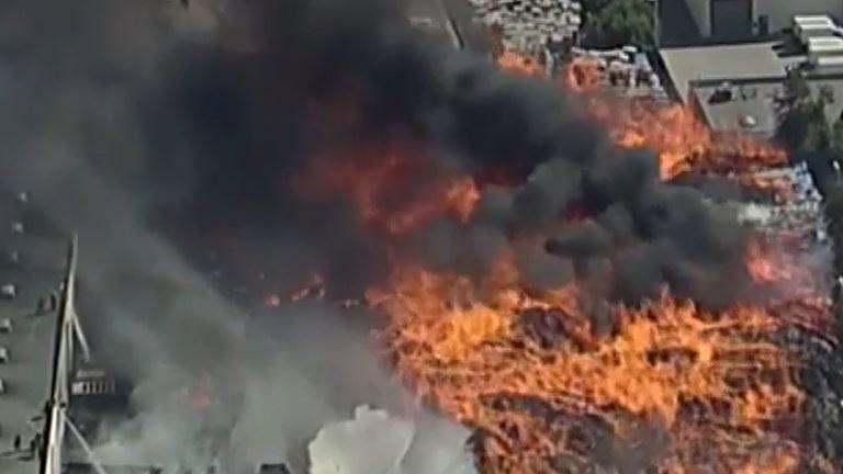 A huge warehouse fire sends thick smoke skyward in California