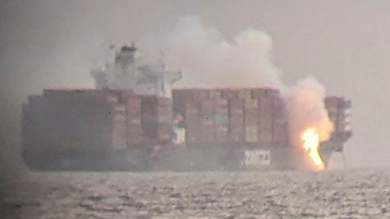 Fire cascades down from the deck of the container ship ZIM Kingston into the waters off the coast of Victoria, British Columbia, Canada, October 23, 2021, as seen through a pair of binoculars, in this image obtained via social media. SURFRIDER FOUNDATION CANADA via REUTERS ATTENTION EDITORS - THIS IMAGE HAS BEEN SUPPLIED BY A THIRD PARTY. MANDATORY CREDIT. NO RESALES. NO ARCHIVES. THIS PICTURE WAS PROCESSED BY REUTERS TO ENHANCE QUALITY. AN UNPROCESSED VERSION HAS BEEN PROVIDED SEPARATELY