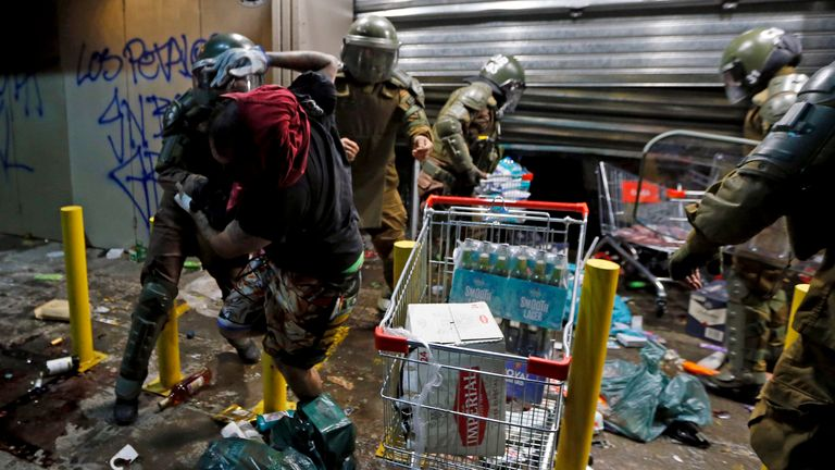Police arrest a person as he tries to loot a supermarket on the two-year anniversary of the start of anti-government mass protests over inequality, in Santiago, Chile, Monday, Oct. 18, 2021. (AP Photo/Luis Hidalgo) PIC:AP