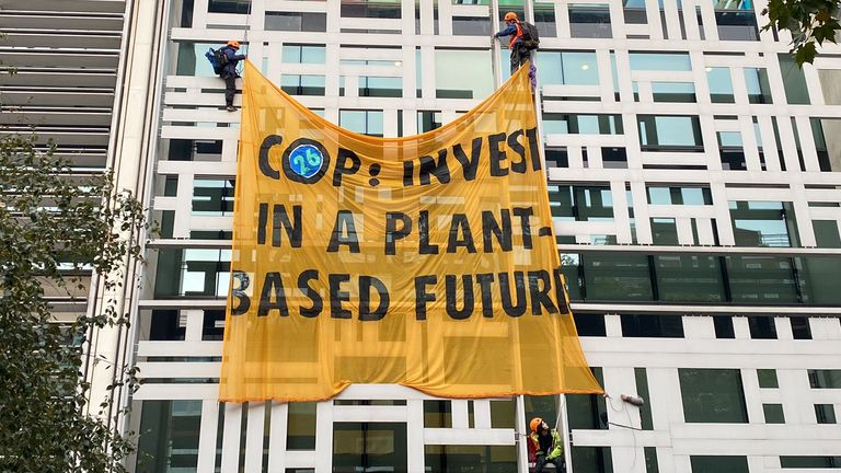 Animal Rebellion protesters have unfurled a banner calling on world leaders to 'invest in a plant-based future'. Pic: Matt Grant