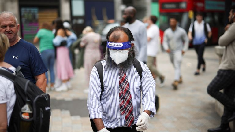 A person wearing a protective face shield and face mask walks through Oxford Circus, amid the coronavirus disease (COVID-19) outbreak, in London