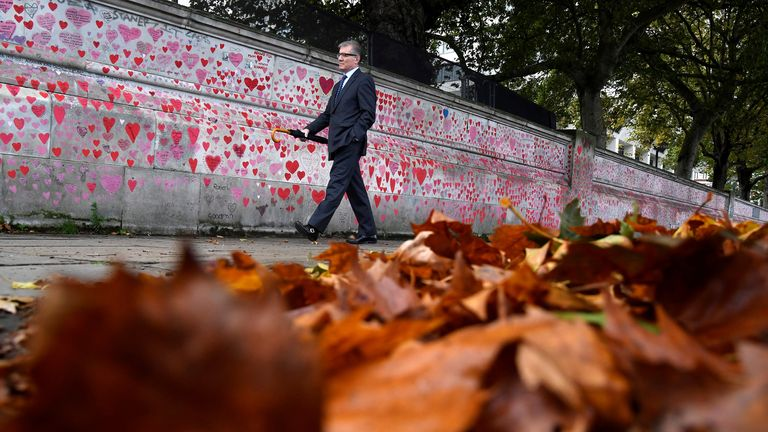 A man walks beside the National Covid Memorial Wall, a dedication of thousands of hand painted hearts and messages commemorating victims of the COVID-19 pandemic, in London, Britain, October 20, 2021. REUTERS/Toby Melville