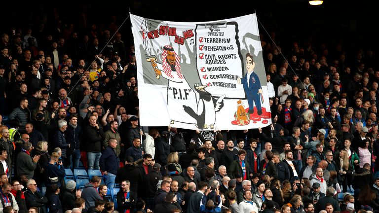 Crystal Palace fans with a banner about Newcastle United's takeover before the match