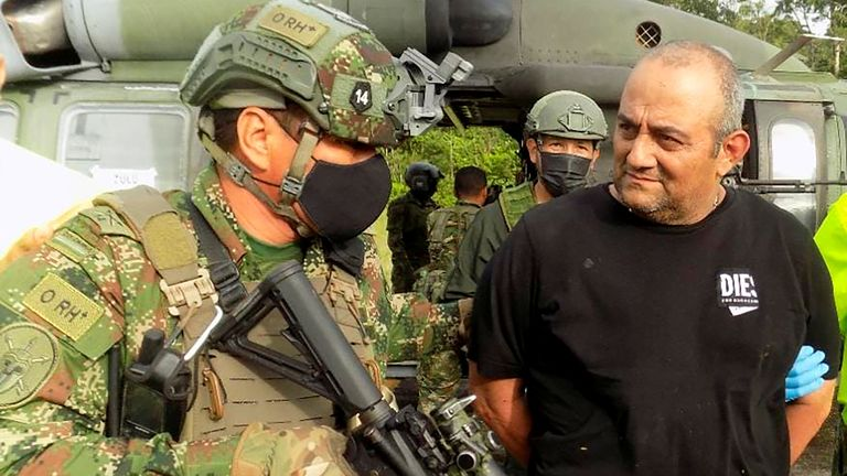 """Dairo Antonio Usuga David, alias """"Otoniel"""", top leader of the Gulf clan, is escorted by Colombian military after being captured, in Turbo, Colombia October 23, 2021. Colombian Defense Ministry/Handout via REUTERS ATTENTION EDITORS - THIS IMAGE HAS BEEN SUPPLIED BY A THIRD PARTY. MANDATORY CREDIT. NO RESALES. NO ARCHIVES."""