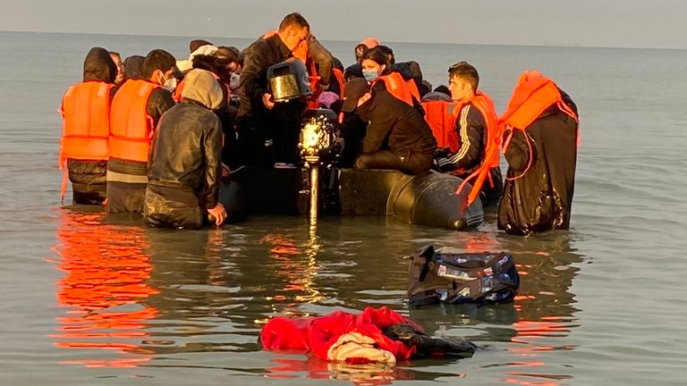 Migrants - manhandling a large inflatable boat down a northern French beach, to get to the seafront in order to to cross the Channel. - re copy from Adam Parsons and Sophie Garratt