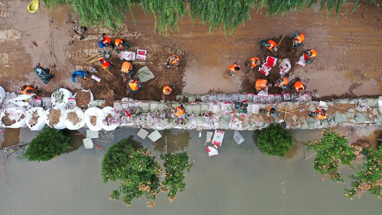 In this photo released by Xinhua News Agency, an aerial photo shows rescuers fortifying temporary dyke against the flood at Lianbo Village in Hejin City in northern China's Shanxi Province on Sunday, Oct. 10, 2021. PIC:AP