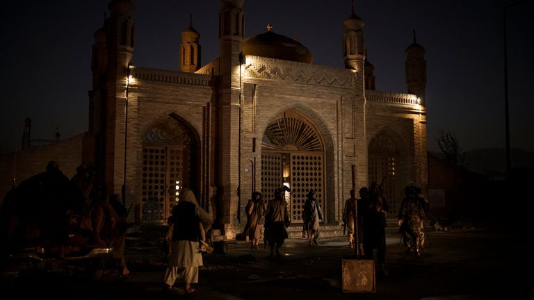 Taliban fighters walk at the entrance of the Eidgah Mosque. Pic: AP