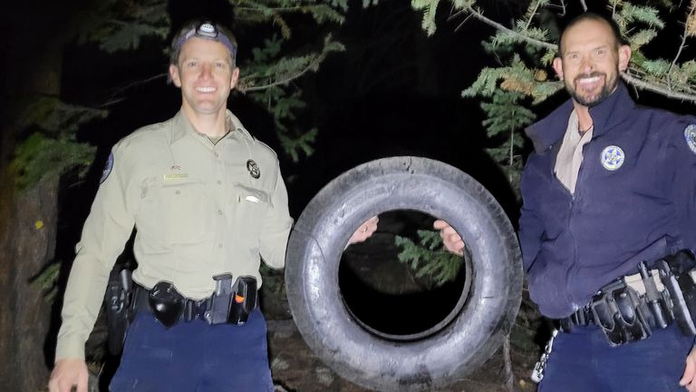 Wildlife officers Scott Murdoch and Dawson Swanson hold up the tire that, according to Colorado Parks & Wildlife report, have been stuck on a bull elk's neck for over two years, in Colorado, U.S., October 9, 2021 in this picture obtained from social media. Pat Hemstreet/via REUTERS THIS IMAGE HAS BEEN SUPPLIED BY A THIRD PARTY. MANDATORY CREDIT. NO RESALES. NO ARCHIVES.