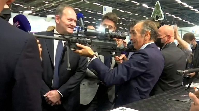 French right-wing commentator Eric Zemmour points an unloaded sniper rifle at journalists.