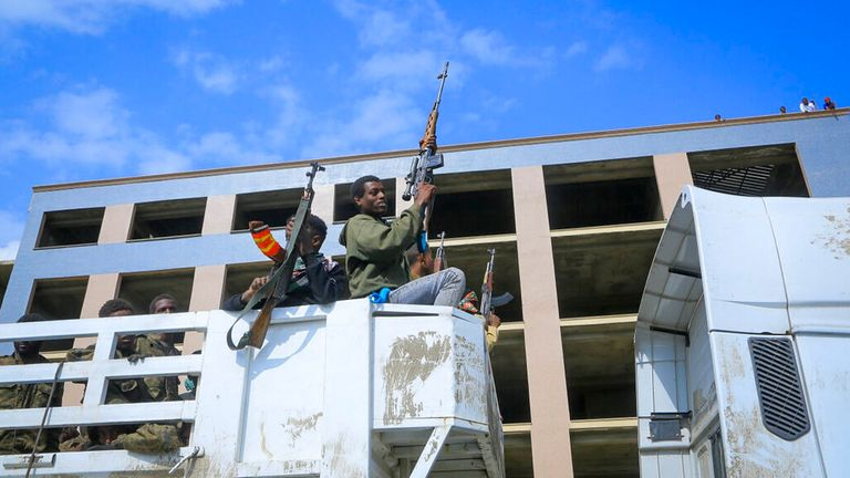 Armed Tigray forces accompany captured Ethiopian government soldiers and allied militia members in Mekelle