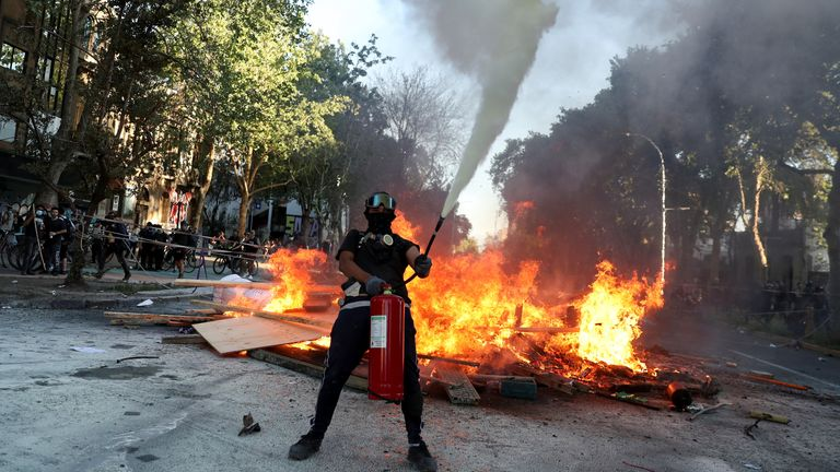 A demonstrator uses a fire extinguisher during a protest against Chile's government on the second anniversary of the protests and riots that rocked the capital in 2019, in Santiago, Chile, October 18, 2021. REUTERS/Ivan Alvarado