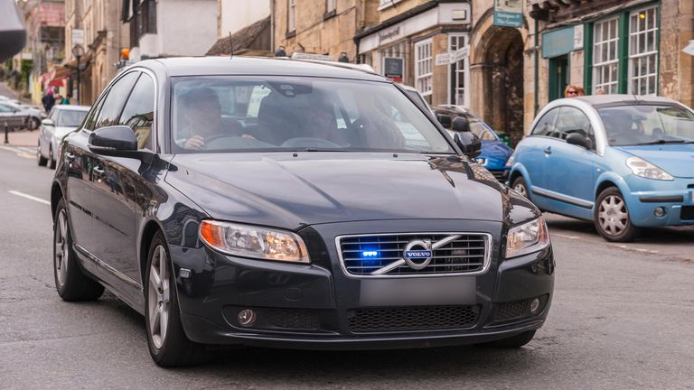 FKKN2J An unmarked police car flashes its blue lights as it speeds through Burford , Oxfordshire , England , Britain , Uk
