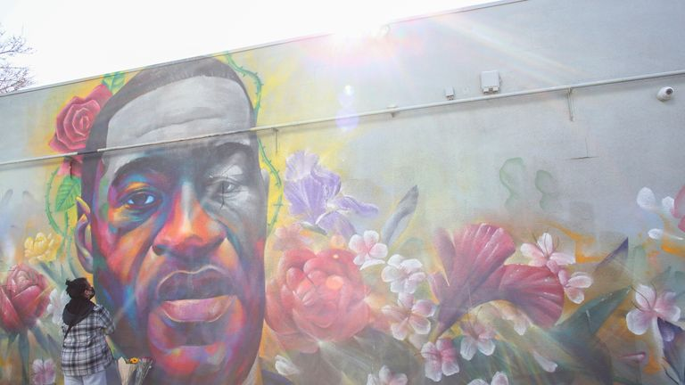A woman pays her respect at a mural of George Floyd after the verdict in the trial of former Minneapolis police officer Derek Chauvin, found guilty of the death of Floyd, in Denver, Colorado